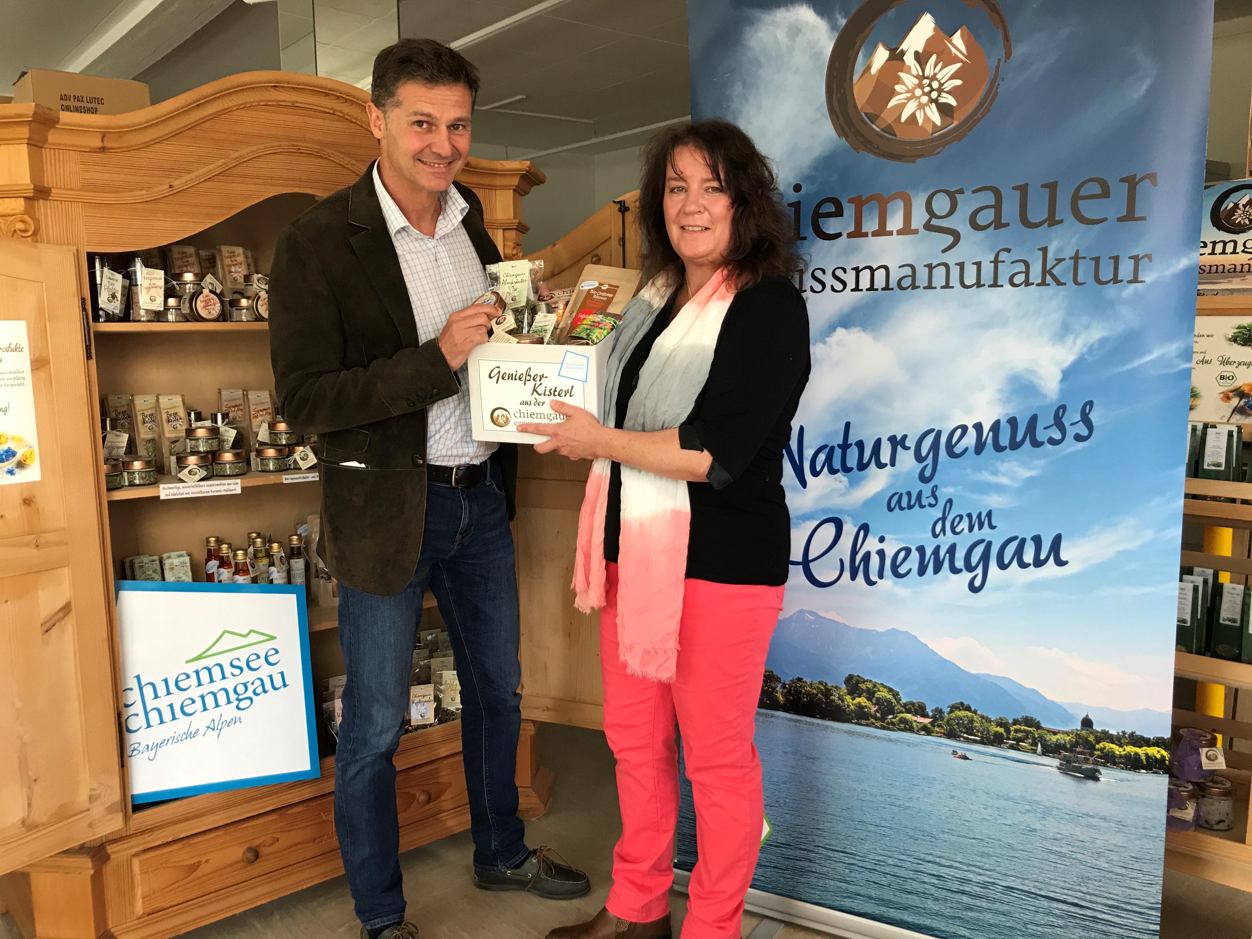 """Zum Start befüllten CT-Geschäftsführer Stephan Semmelmayr und Astrid Günther, Geschäftsführerin der Chiemgauer Genussmanufaktur, eines der neuen """"Genießer-Kisterl"""" gemeinsam."""